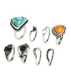 Ringe aus patiniertem Metall in verschiedenen Größen und Ausführungen. Ein Ring mit Plastikperlen in Facettenschliff, zwei Ringe mit Plastikschmuckstein und zwei mit Emailleaufsatz. Die Ringe können sowohl oben als auch unten am Finger getragen werden.