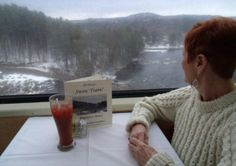 This passenger aboard the Saratoga and North Creek Railway's Snow Train  enjoys breakfast in the dome car while watching snow clad Adirondack scenery glide by.