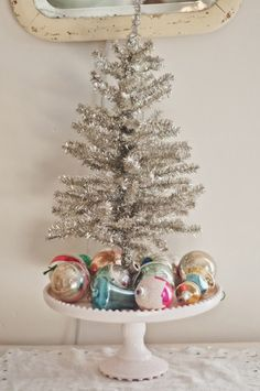 tabletop tinsel tree surrounded by vintage Christmas balls on cake pedestal