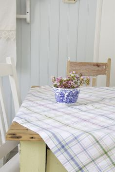 light blue wood, table and flowers and check cloth