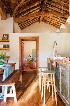 cocina comedor y dormitorio en una casa rustica con tonos rosa