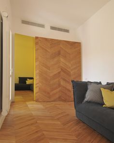 #tissellistudio living room with wooden closets, wooden floor and a yellow coloured mirror