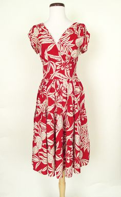 This 1940's inspired rayon print dress is the perfect little summer dress! It features a tropical print of cream flowers and cactus on a deep red background. The bodice is gathered at the shoulders wi