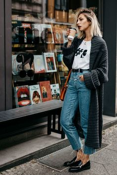 This combo of a dark grey knit open cardigan and blue jeans will attract attention for all the right reasons. Black leather loafers will add elegance to an otherwise simple look.   Shop this look on Lookastic: https://lookastic.com/women/looks/open-cardigan-crew-neck-t-shirt-jeans/23911   — Charcoal Knit Open Cardigan  — White and Black Print Crew-neck T-shirt  — Black Leather Belt  — Tan Leather Crossbody Bag  — Black Leather Loafers  — Blue Jeans