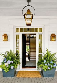 Entryway with woven rug, black front door, and lamp posts
