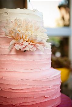 3-tier round with butter cream or cream cheese frosting monochromatic pink applied in a messy horizontal smear with white dahlia accent