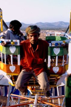 This man works for the Ferris Wheel company in Pushkar. Still running on old generators, he jumps from one rim to another!