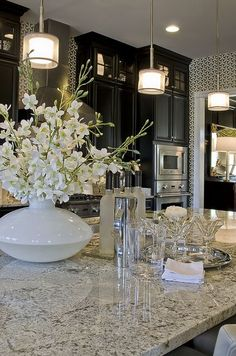 Love the granite and wallpaper together with the light touch of white and glass accessories and the graceful lighting choices. The perfectly well put together room.