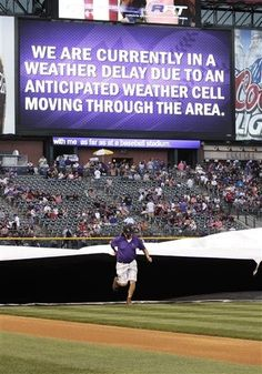 A grounds crew member helps pull a tarp across the infield as the Colorado Rockies against the PIttsburgh Pirates baseball game is delayed due to lightning storms in Denver, Saturday, Aug. 10, 2013.(AP Photo/Joe Mahoney)
