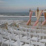 Blush, gold  and ivory fabrics accent this natural arbor at Wrightsville Beach, NC.  Beach set provided by Sweetwater Bamboo Beach Wedding Events.