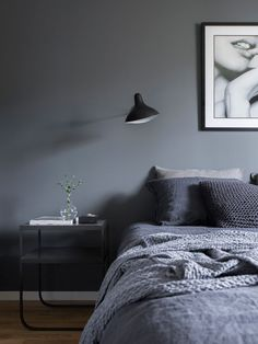 Beautiful grey color bedroom with modern bedside table and photo wall art