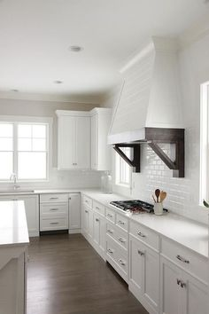 Gorgeous white kitchen is fitted with a white shiplap hood accented with espresso stained corbels and mounted between windows to all white mini subway backsplash tiles above an integrated cooktop.