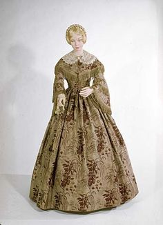 C.1855-1865, American, 2-piece day dress of beige, green & maroon printed silk with a removable lace collar and undersleeves.  Trimmed with garnet-type stone & gold metal buttons and soft green fringe.