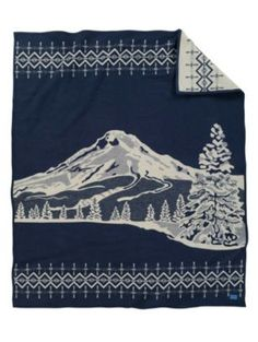 MT. HOOD BLANKET - When Pendleton Woolen Mills founder Thomas Kay arrived in Oregon in 1863, he no doubt saw the site that still impresses first-time visitors today. Majestic Mt. Hood looms above fields & forests, visible up to one hundred miles away. The 11,245-foot mountain, an active volcanic peak in the Cascade Range, is covered with snow most of the year so it's a prized destination for skiers & climbers year-round. Native Americans called it Wy'east after a chief of the Multnomah…