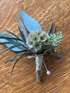 Scabiosa pod accented with eucalyptus, feathers and twine.