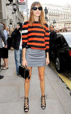Alexa Chung wearing a striped knitted sweater, grey mini skirt, and strappy heels