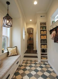 This family-friendly mudroom is actually a covered breezeway between garage and house. There is radiant heat under the terra-cotta tile floors.