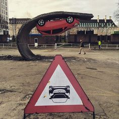 Artist Alex Chinneck creates the illusion of an upside down car stuck to a wave of road.