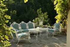 The stone patio on the west side of the house accommodates Mary's vintage iron garden furniture that she had reupholstered in soft blue-green.
