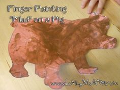 "Finger painting ""mud"" on a pig"