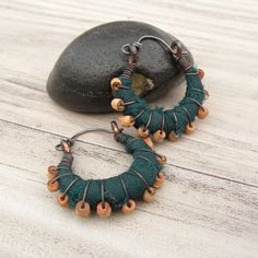 Eclectic, small sized copper hoop earrings that are wrapped in fair trade Indian silk in a dark and earthy forest green color with sterling silver