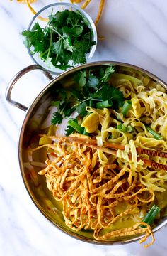 A fantastic recipe for Khao Soi Curry Noodles - Burmese/ Northern Thai dish with egg noodles, curry sauce, chicken, and fried noodles on top.