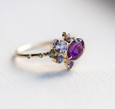 Wild berry jam cluster ring, oval purple garnet clustered with amethyst, teal sapphire, lilac sapphire, tanzanite & London blue topaz gemstones.