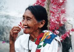 Love this photo of an elderly woman in El Salvador smiling as she inhales a flower's scent.