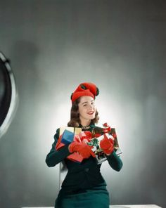 ca. 1942 --- Model in red and green Christmas hat, holding array of gifts in her arms. vintage everyday: Extraordinary Color Fashion Photography Taken During the 1940s by John Rawlings