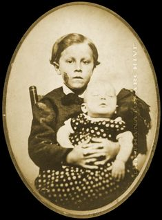 Young boy holding deceased infant sister. Salt print, c.1860