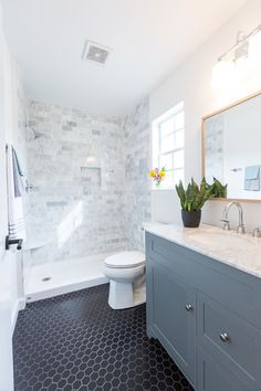 Carrara Marble tile shower surround, Black hex tile, Gray vanity with Carrara marble top, wide spread faucet, White Oak mirror.