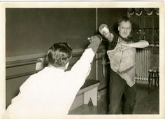 Maître Rohdes, posing for the camera demonstrates how a lesson is given. The Maître is correcting the elevation of the weapon hand by using his foil to bring the student's foil guard to the appropriate height. He is also correcting the placement of the thrust by replacing the point of the students' foil on to the correct position on the plastron.