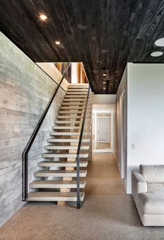 In this modern house, the ceiling contrasts the board formed concrete wall, the lightly colored stairs and the white hallway.