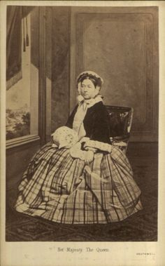 Full length studio portrait of Queen Victoria. She is seated and wearing bonnet, tying under her neck in bow, she is wearing fur trimmed jacket and muff and tartan skirt