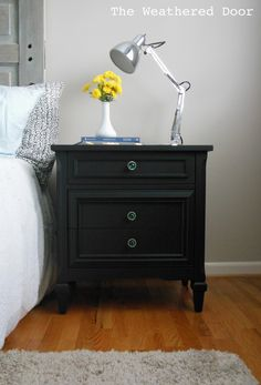 A Pair Of Black Nightstands With Emerald Knobs