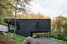 Located in Shefford, Quebec, The Rock is a house designed by Atelier Général that's built into the slope of a mountain and surrounded by maple trees.