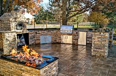 This outdoor kitchen features a brick pizza oven, sink, refrigerator, fire pit, grill and stamped Ashler concrete. Gas Can Kitchens designed and built.