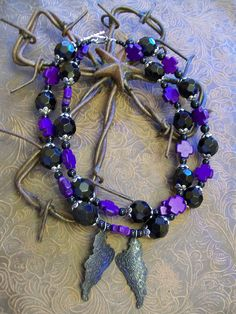 Very cool black and deep purple cross beaded necklace with black angel wing pendants. $35