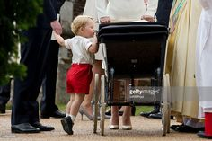 Catherine, Duchess of Cambridge and Prince William, Duke of Cambridge stand as Prince George of Cambridge looks into Princess Charlotte of Cambridge's pram as they leave the Church of St Mary Magdalene on the Sandringham Estate after the Christening of Princess Charlotte of Cambridge on July 5, 2015 in King's Lynn, England.