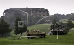 Security police walk past military vehicles on the grounds of the Celtic Manor Resort prior to a NATO summit in Newport, Wales on Wednesday, Sept. 3, 2014. Lashing out at Russia, President Barack Obama on Wednesday cast Moscow's aggression in Ukraine as a threat to peace in Europe. He vigorously vowed to come to the defense of NATO allies that fear they could be Vladimir Putin's next target. NATO heads of state meet for a two-day summit beginning on Thursday. (AP Photo/Virginia Mayo)