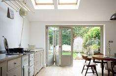Love the large folding doors that open this simple kitchen to outside. Devol Shaker Kitchen Remodelista Open to Garden Devol Shaker Kitchen, Devol Kitchens, Shaker Style Kitchens, Home Kitchens, Kitchen Doors, Open Plan Kitchen, New Kitchen, Kitchen Dining, Loft Kitchen