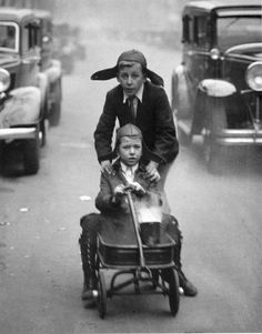 Martin Munkacsi: Madrid, 1930 | children playing | black & white vintage photography | boys | traffic | street scene | hitching a lift | brothers | siblings | friendship | fun | those marvellous young men and their machines