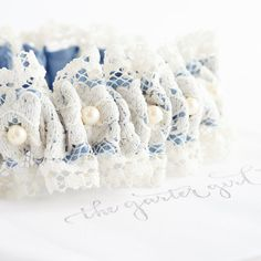 A wedding garter made with vintage wedding dress lace detailed with something blue satin and pearls. A hand made bridal garter heirloom from The Garter Girl.