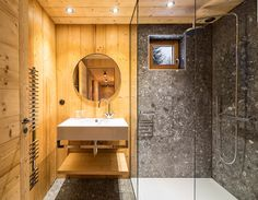 In this rustic modern bathroom, wood walls and ceiling have been paired with stone tiles and a glass shower partition.