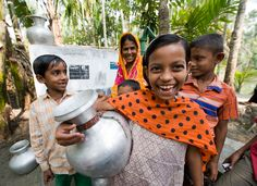Kids in rural Bangladesh smile near a charity: water project in their village.