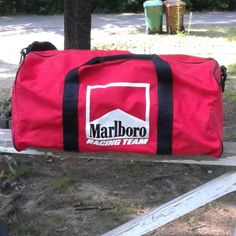 """This is a used Marlboro Racing Team Men's Gym Bag, it is red, black and white. It is 20"""" in length, 9"""" height, 9"""" wide. It has a small black stain on the bottom of the bag. it has a zipper pocket on the back, and an open pocket on one side and a zipper pocket on one side. it has shoulder strap and handles. it zips on top. there are no holes or tears on the bag. Please view the pictures and if you have any questions please ask."""