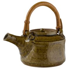 Warren MacKenzie Ash Glazed Stoneware Teapot   Graceful, balanced, easy to handle, and expressive. The clay body is light brown stoneware with specks of iron. Faceted with an inset lid and surprisingly light for stoneware. It has a greenish/amber ash glaze with a rattan handle. Stamped on the side with the artist's initials.