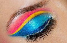 maquillage des yeux arc-en-ciel en bleu, jaune et rose et un trait d'eye-liner pailleté