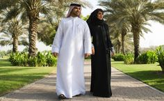 As part of tradition, Emirati women wear the abaya, a long black robe with a sheila (head scarf), while Men wear the dishdash or kandurah (long white robe) and the headscarf (ghotra). Men Dress, Duster Coat, Women Wear, How To Wear, Jackets, Long Black, Dubai, Beautiful, Dresses
