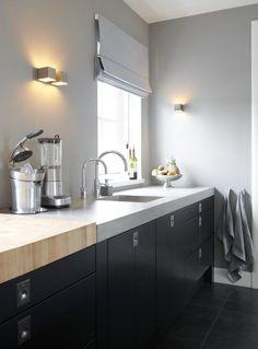 Une cuisine toute simple en noir - le plan de travail se transforme en billot en bois pour découper.